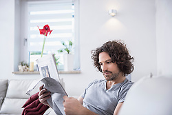 Man sitting on couch and reading a newspaper, Munich, Bavaria, Germany