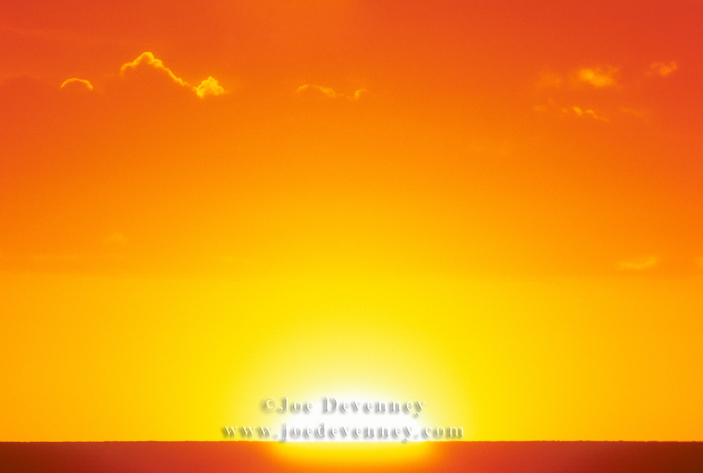 Very large sun rising over the ocean's horizon