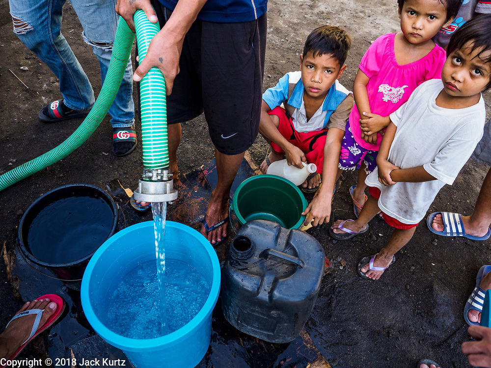 24 JANUARY 2018 - LIGAO, ALBAY, PHILIPPINES: Evacuees line up for water at an evacuation center in a school in Ligao. The Mayon volcano continued to erupt Tuesday night and Wednesday forcing the Albay provincial government to order more evacuations. By Wednesday evening (Philippine time) more than 60,000 people had been evacuated from communities around the volcano to shelters outside of the 8 kilometer danger zone. Additionally, ash falls continued to disrupt life beyond the danger zones. Several airports in the region, including the airport in Legazpi, the busiest airport in the region, are closed indefinitely because of the amount of ash the volcano has thrown into the air.    PHOTO BY JACK KURTZ
