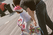Father teaching his daughter to ride her pink bike