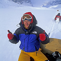 BAFFIN ISLAND, Nunavut, Canada. Jared Ogden (MR) exults as expedition snowmobiles up Stewart Valley to Sail Peaks (bkg).