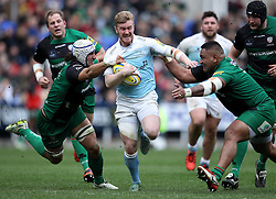 Newcastle Falcons' Tom Catterick carries the ball as London Irish's Halani Aulika and London Irish's Blair Cowan try to tackle- Photo mandatory by-line: Robbie Stephenson/JMP - Mobile: 07966 386802 - 28/03/2015 - SPORT - Rugby - Reading - Madejski Stadium - London Irish v Newcastle Falcons - Aviva Premiership
