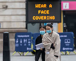 © Licensed to London News Pictures. 29/12/2020. London, UK. Members of the public walk past a Covid-19 information display in Westminster, London as NHS chiefs say that health workers are back in the eye of the storm as cases soar throughout London and the UK. Ministers are expected to roll out vaccinations to start from the 4 January 2021 as they mull over putting parts of the country into tier 5 restrictions to slow the spread of the virus. Last week Health Secretary Matt Hancock announced another new Covid-19 mutation has been discovered in the UK as Downing Street ordered many more areas of England to go into Tier 4 lockdown with tougher new Covid-19 restrictions for many as the mutated strains continue to spread throughout the UK. Photo credit: Alex Lentati/LNP