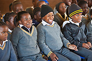Children from Matsie Steyn primary school, Sharpeville, Vereeniging, South Africa, watch a performance of the 'No Monkey Business' puppet show, an AREPP: Theatre for Life production providing interactive social life skills education to school children through theatre productions. They are based in Johannesburg, South Africa and are on tour for 3 months doing performances everyday at schools across the country.