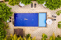 Aerial view of attractive girl floating over water at resort, Bali, Indonesia.