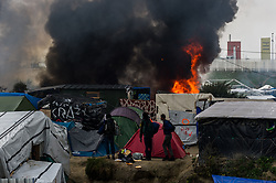 October 26, 2016 - Calais, France - Migrants look in the Calais Jungle at a burning hut. Huge fires destroyed a mayor part of the refugee camp today. (Credit Image: © Markus Heine/NurPhoto via ZUMA Press)