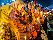 05 DECEMBER 2014 - BANGKOK, THAILAND: Thai Muslims hold lit candles for the King's Birthday on Sanam Luang in Bangkok. Thais marked the 87th birthday of Bhumibol Adulyadej, the King of Thailand,  Friday. The King was born on December 5, 1927, in Cambridge, Massachusetts. The family was in the United States because his father, Prince Mahidol, was studying Public Health at Harvard University. He has reigned since 1946 and is the world's currently reigning longest serving monarch and the longest serving monarch in Thai history. Bhumibol, who is in poor health, is revered by the Thai people. His birthday is a national holiday and is also celebrated as Father's Day. He is currently hospitalized in Siriraj Hospital, recovering from a series of health setbacks.     PHOTO BY JACK KURTZ