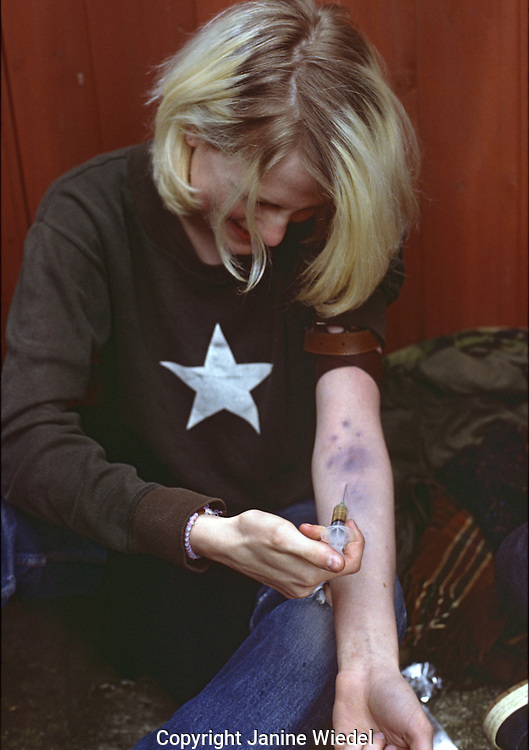 Young woman addict injecting  heroin.