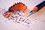 Sharpened pencil and scraps on white background