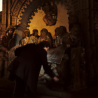 Woman leaving a coin in the donation box at the Coimbras chapel, only open during Semana Santa.