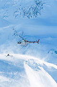 Helicopter making a touchdown to pick up heliskier in Chugach mountains.