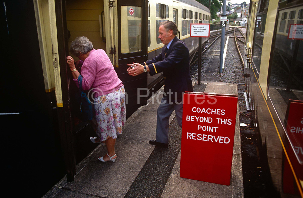 A volunteer helps an elderly lady from the platform up into a train carriage at the Paignton steam museum. The old passenger steps up from platform level into the train carriage and there to help is the museum official who comes towards her with arms out to help steady her if she stumbles. The Paignton & Dartmouth Steam Railway is a 6.5 miles (10.5 km) heritage railway on the former Kingswear branch line between Paignton and Kingswear in Torbay, Devon, England. The line was built by the Dartmouth and Torbay Railway, opening to Brixham Road station on 14 March 1861 and on to Kingswear on 10 August 1864
