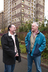Tenant and housing officer in front of flats.