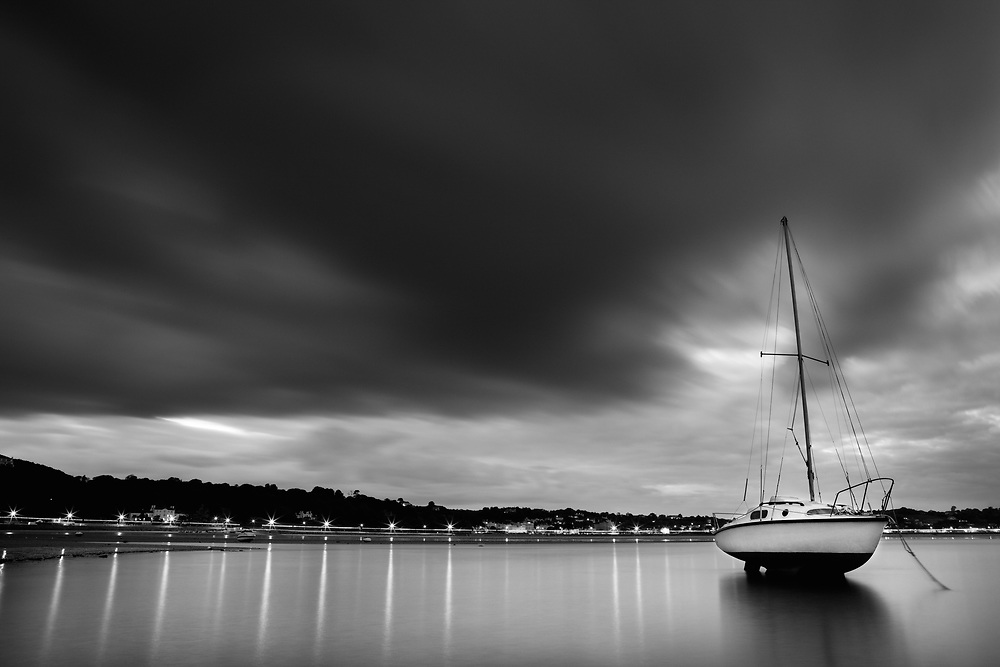 Yacht moored up in glassy calm water with dark moody clouds above, in the evening at St Aubin's Bay in Jersey, Channel Islands