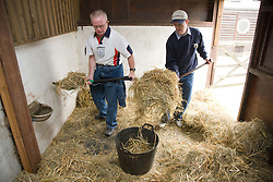 Two men with learning disabilities helping to muck out a stable on a trip to an animal centre,