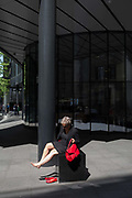 A woman rests her feet in a small area of sunlight on Fenchurch Avenue in the City of London - the capitals financial district, on 6th June 2018, in London, England.