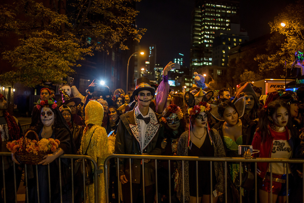 New York, NY - 31 October 2015. A crowd behind police barriers waits its turn to enter the parade route on 6th Avenue for the annual Greenwich Village Halloween Parade.
