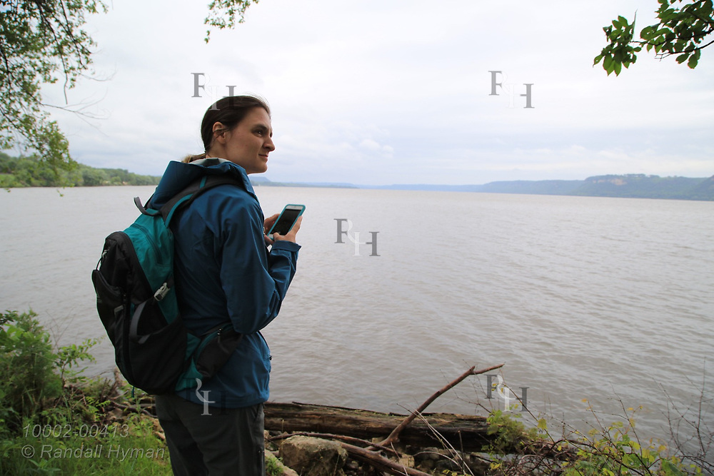 Young woman looks across Lake Pepin on the Mississippi River; Lake City, Minnesota.