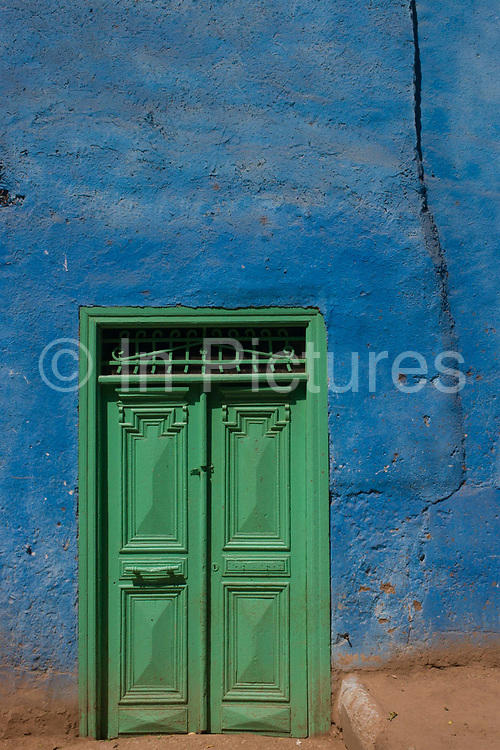 Local architecture of a green door and blue painted house in in a village near Medinet Habu on the West Bank of Luxor, Nile Valley, Egypt. This scene is typical of the quiet pace of rural everyday life, far away from the chaotic capital, Cairo whose government controls the policies that affect the people of small villages.