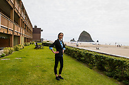 Sheryl Paul, front desk clerk at the Surfsand Resort in Cannon Beach, Oregon, standing on the lawn that faces the Pacific Ocean with iconic Haystack Rock in the distance.