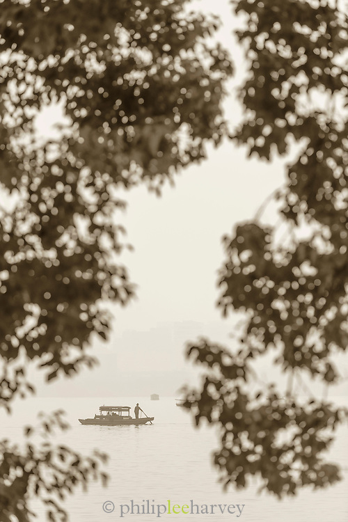 Black and white landscape with view of silhouetted trees, boat and lake at dawn, West Lake, Hangzhou, Zhejiang Province, China