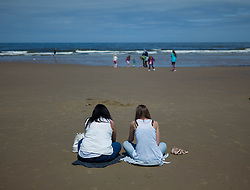 © Licensed to London News Pictures. 01/06/2013<br /> <br /> Saltburn Beach, Cleveland, Untied Kingdom<br /> <br /> On the first day of summer two girls sit on the beach as they visit Saltburn to enjoy the warm weather.<br /> <br /> Photo credit : Ian Forsyth/LNP© Licensed to London News Pictures.