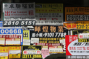 A wall of ad postings in the center of Hong Kong becomes a piece of graphic art