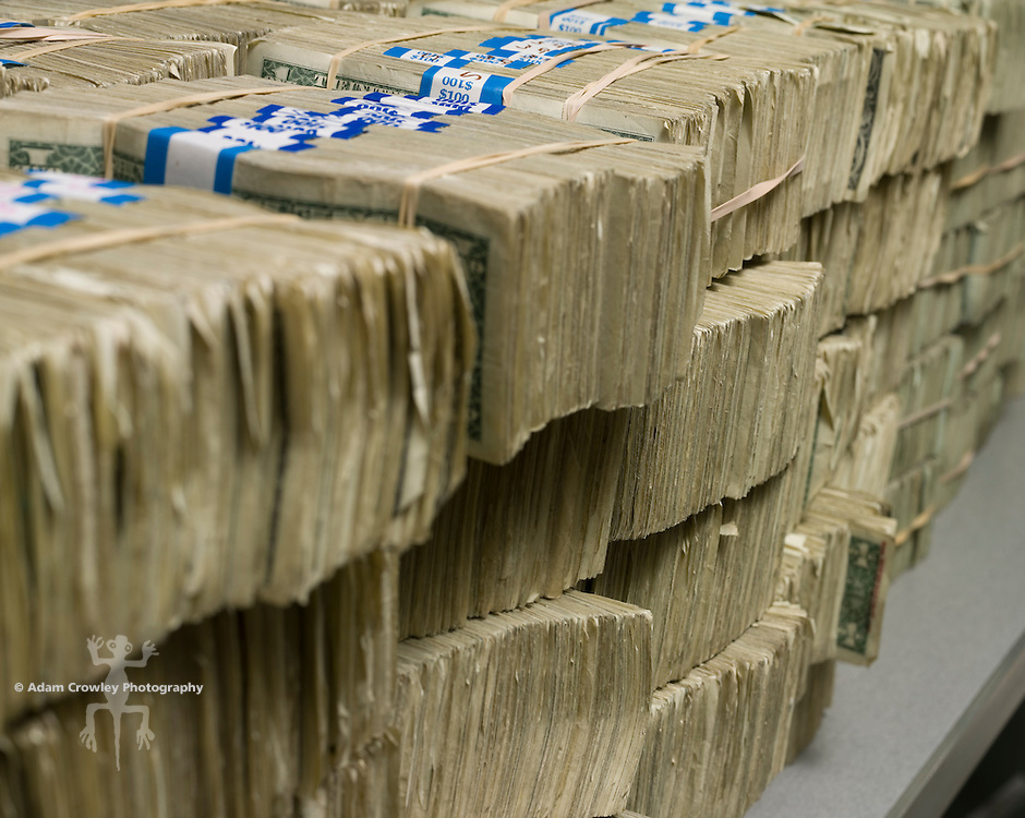 Bundles of U.S. dollar bills, stacked on a table.
