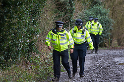 Harefield, UK. 14 January, 2020. Police officers walk along a public right of way from a Stop HS2 protection camp currently being evicted by enforcement agents working on behalf of HS2. 108 ancient woodlands are set to be destroyed by the high-speed rail link and further destruction of trees for HS2 in the Harvil Road area is believed to be imminent.