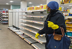 © Licensed to London News Pictures. 25/09/2020. London, UK. A woman wearing a face mask and gloves walks past empty shelves in Boots supermarket in London, as essential items start to run out, amidst a possible second lockdown due to a rise in COVID-19 cases. A number of supermarkets are restricting shoppers from bulk-buying products such as flour, pasta, toilet rolls and anti-bacterial wipes. Photo credit: Dinendra Haria/LNP