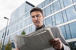 Businessman looking shocked while reading newspaper, Bavaria, Germany