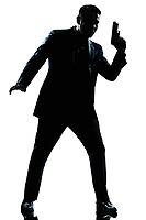 one caucasian spy criminal policeman detective man holding gun full length silhouette in studio isolated white background