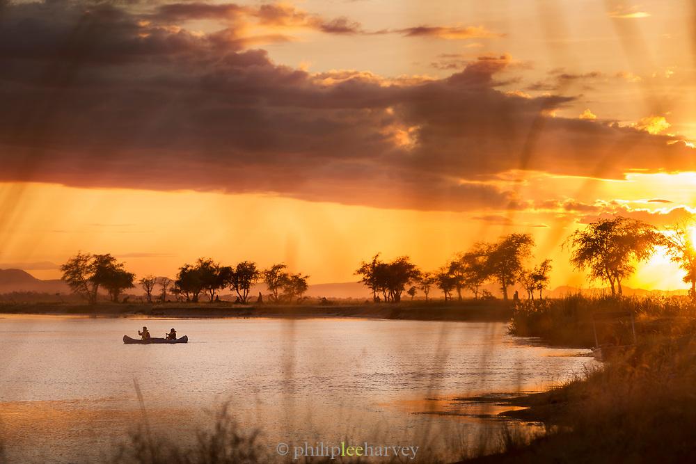 Tourists on canoe safari at sunset on lower Zambezi River in Zambia