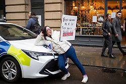 © Licensed to London News Pictures. 12/12/2020. Manchester, UK. A woman poses by a police car as crowd marches through Manchester with with signs for North Unites protest in Piccadilly Gardens, Manchester. Piers Corbyn is expected to make a speech later. Photo credit: Kerry Elsworth/LNP