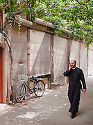 A priest walks through the quiet streets of a souq, before the stalls open, in the early morning. Old City, Damascus, Syria