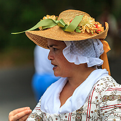 Lancaster, PA, USA - June 9. 2012: Colonial woman wearing huse cap and straw hat at a British America reenactment camp.