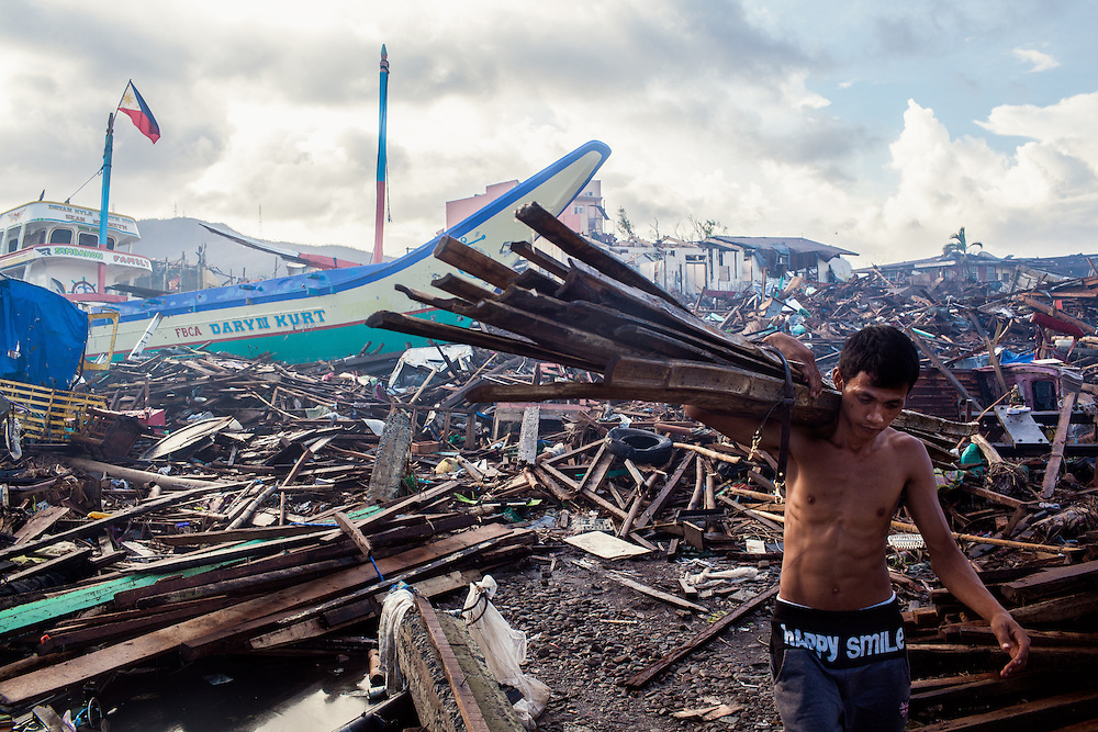 A man carries a pile of salvageable woods to be used to rebuild his damaged house.
