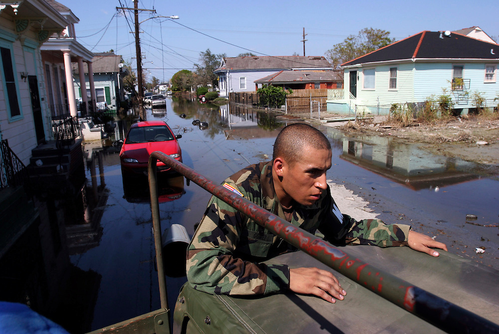 Spec. Roberto Gomez of the 1186th Military Police braces himself on the door frame of a Humvee to avoid contact with contaminated water while searching for survivors in flooded New Orleans homes. Oregon National Guard troops work in New Orleans after the wrath of Hurricane Katrina. Photographed September 8, 2005. (Thomas Patterson / Statesman Journal)
