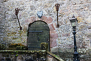 An old door marks the entrance to Comlongon Castle, a restored Medieval Scottish tower house dating from the late 1400s. Guests can stay in the attached Edwardian hotel, a baronial style mansion built 1900-02, set in 120 acres of manicured gardens, sweeping lawns, carp pond, lakes and woodlands, near Clarencefield and Dumfries, in southwest Scotland, United Kingdom, Europe. Originally built by the Murrays of Cockpool, Comlongon Castle remained in the Murray family until 1984. The castle is 50 feet square and stands 70 feet high, with walls over 4 meters thick, with impressive displays of weapons, armor and banners.