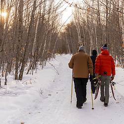 Three men preparing to go snowshoeing at Loon Echo Land Trust's Bald Pate Mountain Preserve in South Bridgton, Maine.