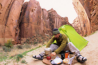 A young man lights his backcountry stove while camping in the Paria Canyon-Vermillion Cliffs Wilderness area, Arizona.