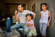 2014/11/23 – Quimili, Argentina: Juan Yedro (44) drinks mate, a traditional South American caffeine-rich infused drink while he spends time with his daughters Jenny Yedro (7) and Janet Yedro (2) at his home in allotment 4 of the Guaycurú Indigenous Community. The people in the area are being threaten by soy producers that see their land as an opportunity to grow more of the crop. On the otherhand indigenous defend a sustainable agriculture and to live in harmony with the nature. (Eduardo Leal)