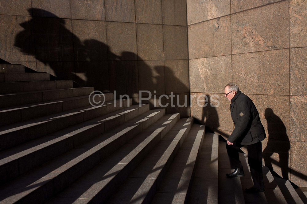 Elderly man struggles up steep steps with the shadows of others on nearby wall form against the panelling of 1980s architecture, located on the south side of London Bridge in the London borough of Southwark. He places a weary foot on the next step as he makes progress upwards towards the top of these stairs