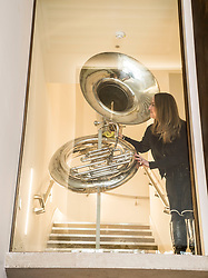 Learning & Engagement Curator Sarah Deters cleans a 1930's sousaphone now on display above the entrance to  the newly-refurbished St Cecilia's Hall, which has just undergone a 2 year, £6.5 million refurbishment which will see more of the University of Edinburgh's musical instrument collection on display to the public.<br /> <br /> © Dave Johnston/ EEm
