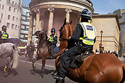 Mounted police arrive swiftly as smoke from flares clears between protesters of the Free Tommy Robinson demonstration, and their opposition organised by anti-fascist groups including Stand up to Racism who are opposed to far right politics on 24th August 2019 in London, United Kingdom. Some 250 Stand Up To Racism and other anti-fascist groups took to the streets today in opposition to supporters of jailed 'Tommy Robinson' real name Stephen Yaxley-Lennon at Oxford Circus, who gathered outside the BBC.