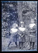 three little girls with identical dress holding flowers  France ca 1920s