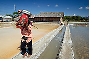Mar 23, 2009 -- SAMUT SONGKHRAM, THAILAND: A worker carries a water pump out to a salt field near Samut Songkhram, Thailand. The salt farms between Samut Sakhon and Sumat Songkhram are Thailand's largest salt producing region. Salt is typically harvested for about six months of the year. The fields are prepared for salt farming as soon as the rainy season ends. First the fields are tamped down so they hold water, then they are flooded with salt water from either the Gulf of Siam or the Mae Khlong River (both are salty). After about two months, the first harvest is ready. The fields are drained and the salt picked up from the fields. Then the fields are flooded again and the process repeated. As the season goes on and the fields become saltier, the amount of time they are flooded is reduced till the end of the season when they may only be flooded for two or three days. Most of the workers in the salt fields are migrant workers from Isaan, an impoverished region in the northeast of Thailand. Once the rainy season starts and it's no longer possible to harvest salt the workers go home to work their small farms. The workers are paid based on the amount of salt their crew harvests.    Photo by Jack Kurtz