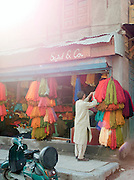 Man looking through colourful fabrics at a shop in Srinigar, Kashmir, India
