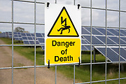 Danger of Death warning signs on the external fence of Salhouse Solar Park has an electrical output of 4.987 MW saving emissions of 4890 tonnes of C02 per year. Norfolk. UK.