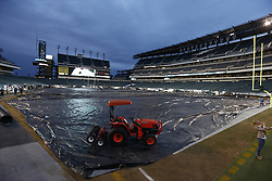 A Kubota tractor weighs down a tarp covering the playing surface at Lincoln Financial Field during the rain before the NFL game between the Chicago Bears and the Philadelphia Eagles on Sunday, December 22nd 2013 in Philadelphia. (Photo by Brian Garfinkel)